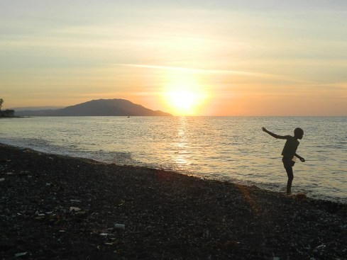 A boy throws stones into the ocean during sunset in Petit Goave, Haiti.